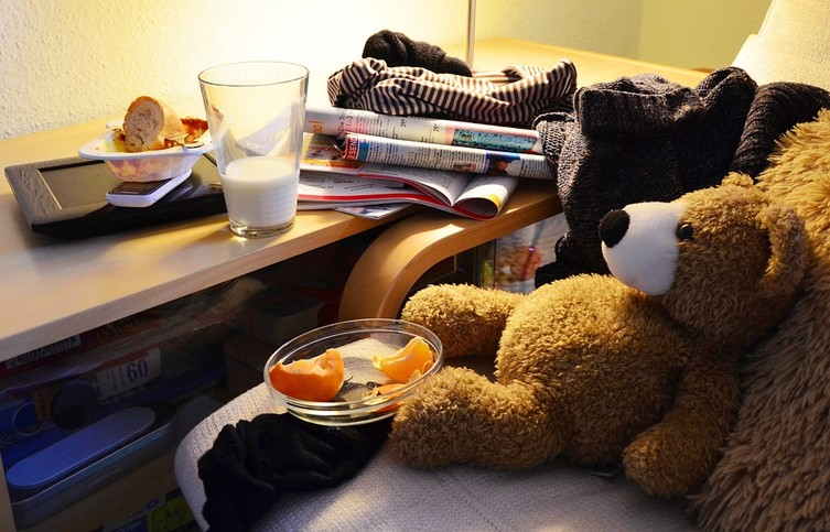 A messy desk with a teddy bear sitting on the desk chair.